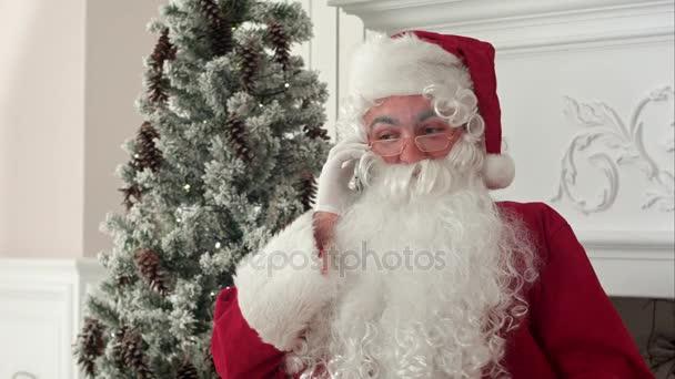 Santa Claus mluví po telefonu, který si přeje Veselé Vánoce
