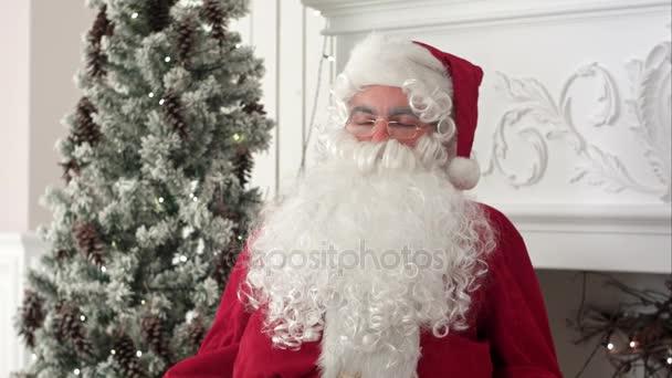 Unavený Santa Claus probuzení z zdřímnout pokračovat v přípravě vánoční dárky