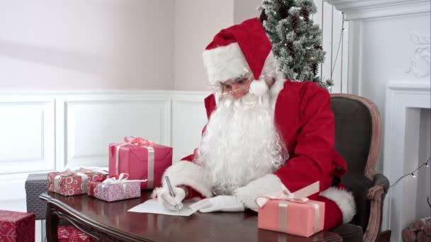 Santa Claus kontrola dárky a dělala si poznámky v seznamu přání dětí