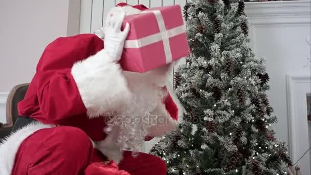 Santa Claus otevření jeho pytel a dávat dárky pod vánoční stromeček
