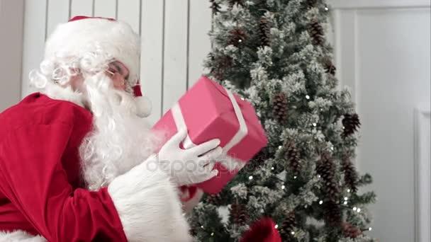 Santa Claus s dárky z jeho vaku uner vánoční stromeček