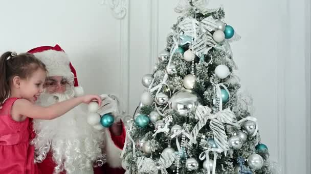 Santa Claus with pretty little girl decorating Christmas tree