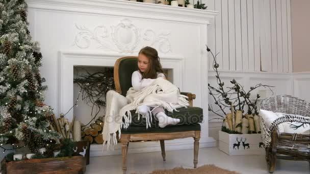 Malá holčička útulně zabalený do deky seděl na židli u vánočního stromu