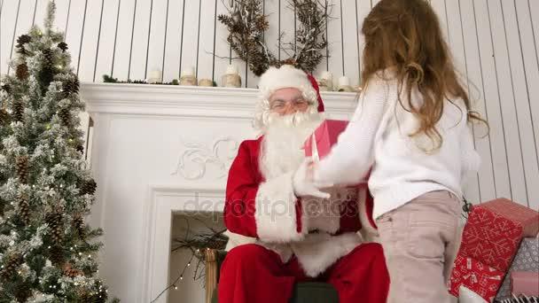 Malá holčička přinášíme dárek pro Santa a huggnig ho v jeho vánoční dílna