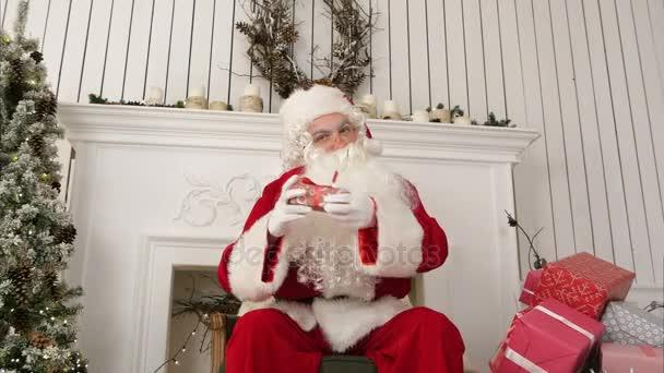 Gute alte Weihnachtsmann sitzt auf einem Stuhl vor dem Kamin, beschreibt, welche Geschenke bereitete er sich auf Weihnachten