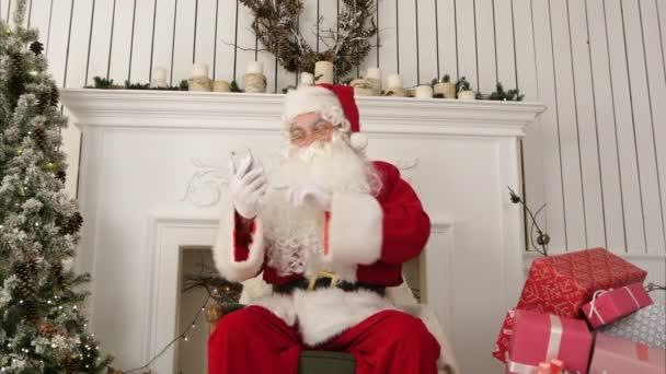 Lachender Weihnachtsmann liest Weihnachtsbotschaften von Kindern vor