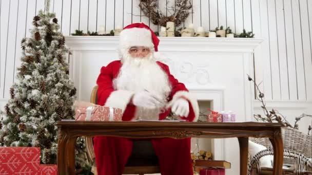 Santa odpovědi na dopisy ve své dílně a vysvětlí, co je to jako být Santa