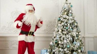 Santa Claus dělá moderního tance u vánočního stromu