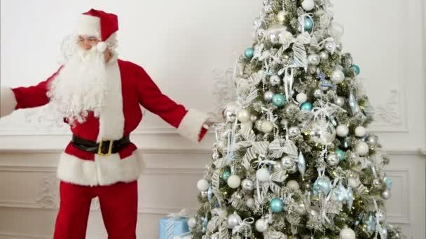 Weihnachtsmann beim lustigen Robotertanz neben dem Weihnachtsbaum