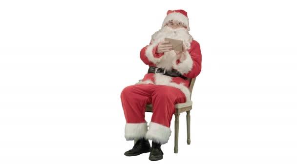 Santa Claus sedí na židli s písmeny v ruce na bílém pozadí