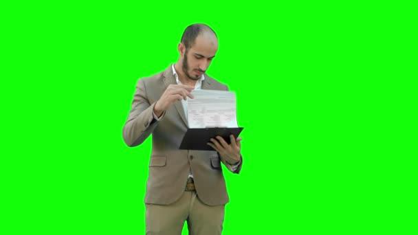 Koncentrovaná podnikatel čtení finanční zpráva o Green Screen, Chroma Key