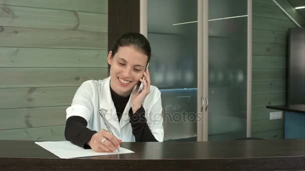 Smiling spa receptionist talking to client over the phone and filling in form