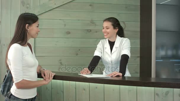 A spa receptionist greeting a female customer at the welcome desk