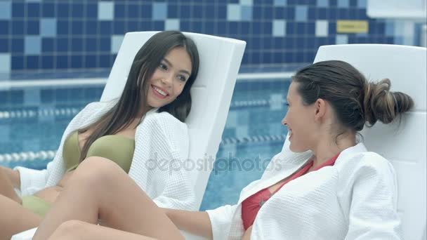 Two beautiful women lying on poolside chaise longues indoors and talking