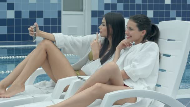 Two beautiful women taking selfies lying on chaise longues near the swimming pool