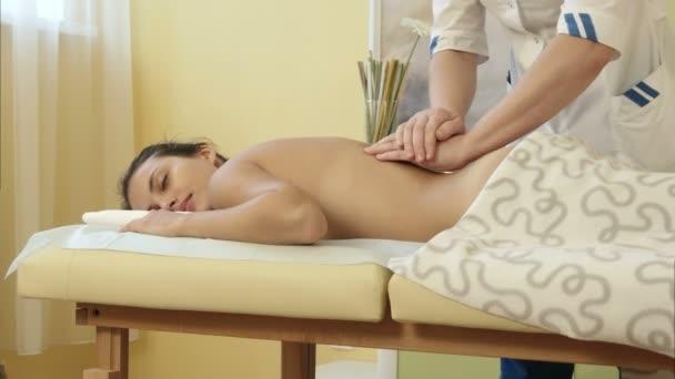 Krásná žena přijímá relaxační masáž zad na spa salon