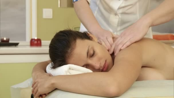 Young woman enjoying shoulder massage in a spa