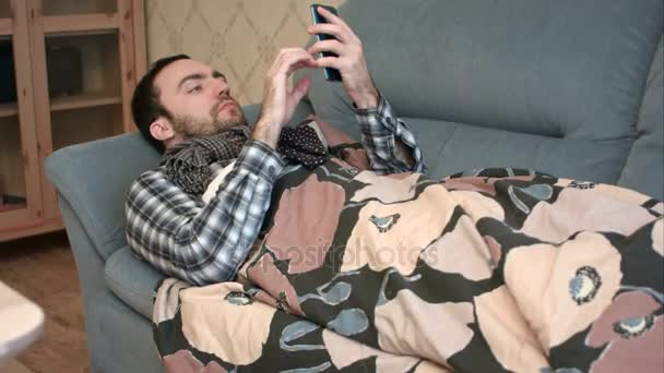 Sick man in scarf lying on the sofa and using phone