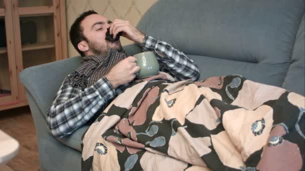 Kranker junger Mann trinkt heißen Tee oder Fiebermittel im Bett