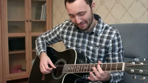 Mladý muž hraje kus těžké kytara sedí na pohovce
