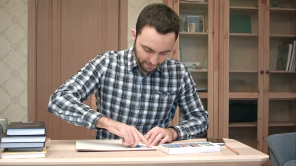 Happy young man drawing sitting at desk at home