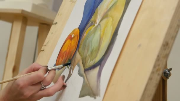 Womans hand painting pumpkin still life with watercolors on easel