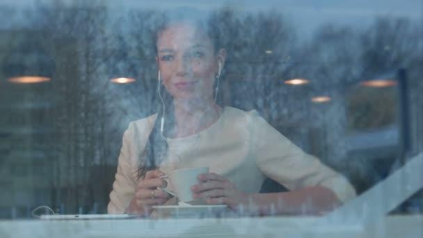 S úsměvem mladá žena v kavárně s sluchátka poslouchat hudbu z tabletu