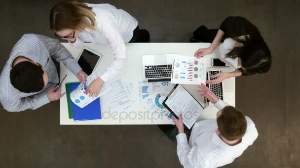 Group of office workers discussing business diagrams and graphs