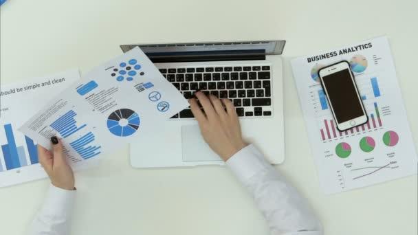 Podnikání žena ruku psaní na klávesnici notebooku s finanční grafy na stůl