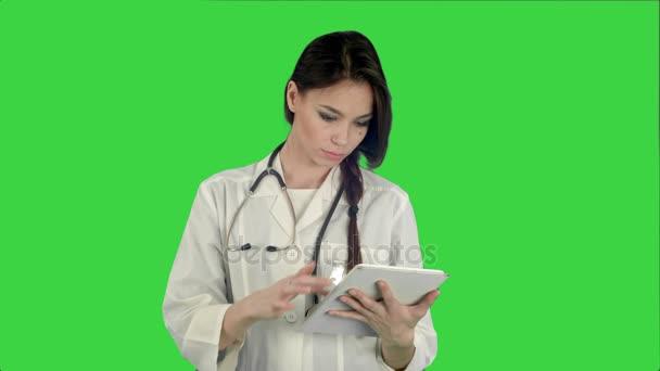 hübsche Ärztin mit Stethoskop mit Tablet-Computer auf grünem Bildschirm, Chroma-Schlüssel