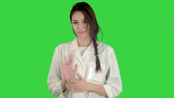 Lächelnde junge Frau im Laborkittel, die auf einem grünen Bildschirm einen lustigen Tanz macht, Chroma-Schlüssel