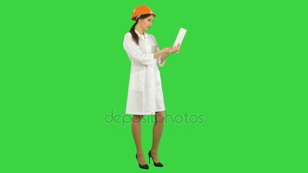 Female engineer in helmet having video call via tablet on a Green Screen, Chroma Key