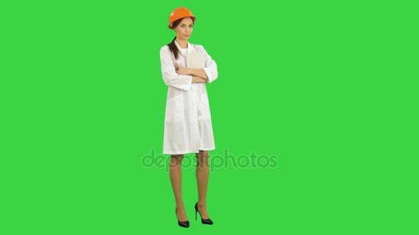 Ženské stavbyvedoucí v přilba držení tabletu mluví do kamery na zelené obrazovce, Chroma Key
