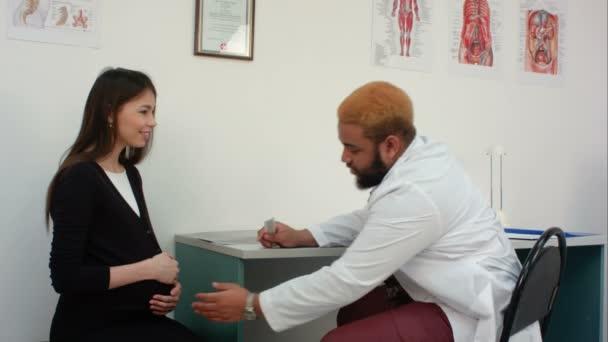 lékař zkoumá břicho těhotné ženy