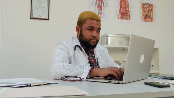 Concentrated Afroamerican young doctor using laptop at his desk
