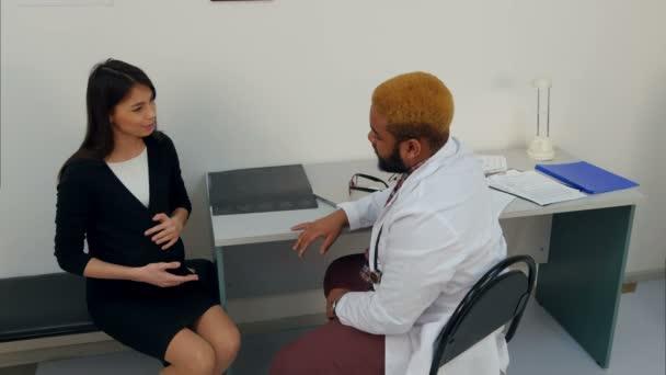 Arzt untersucht Bauch einer Schwangeren