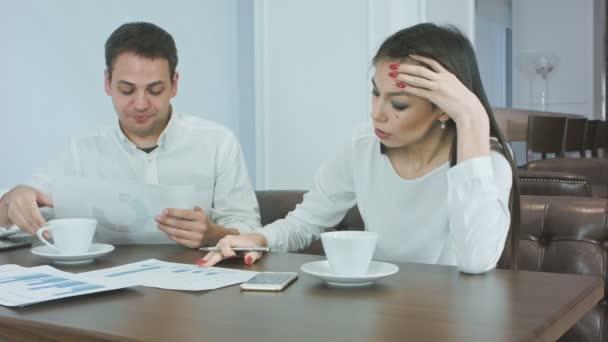 Unavený obchodní partneři pracují na projektu během oběda v kavárně