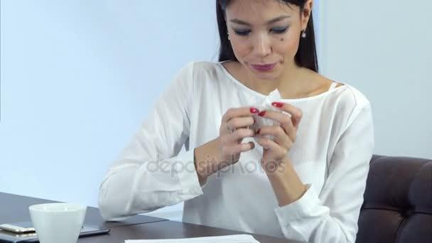 Nemocné ženy kýchání a vysmrkala při podepisování dokumentů v kavárně