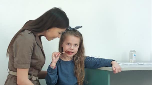 Matka mluví s holčičkou jíst lízátko v kanceláři lékaři