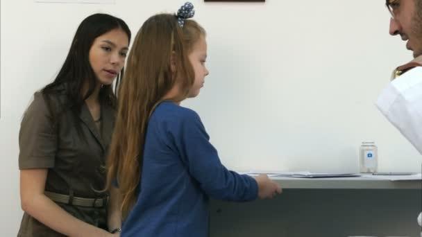 junge Mutter mit Mädchen wird von Kinderarzt mit Stethoskop untersucht