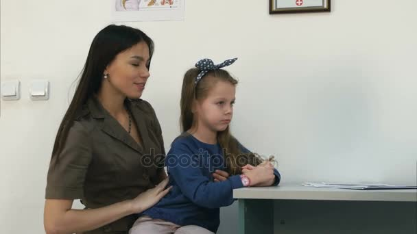 Mladá maminka pyšná její Holčička a lékař jí dal lízátko po zkoušce
