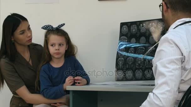Arzt zeigt glücklichen und erleichterten Frau mit kleinem Mädchen Röntgenbilder des Gehirns