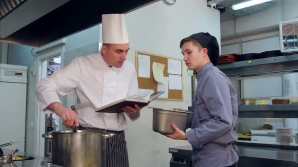 Šéfkuchař s učňů mladý kuchař v kuchyni připravuje pokrm z kuchařky