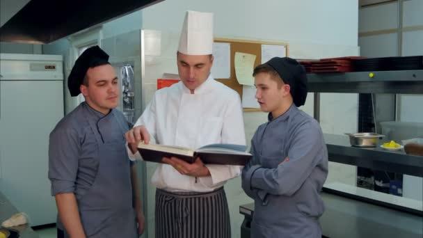Šéf kuchař recept knihu a diskutovat o něco s jeho účastníků