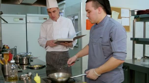 Šéfkuchař s pokynem kuchařka vaříme trainee jak smažit krevety