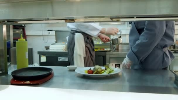 Kuchaři učí mladý praktikant, jak sloužit omáčka