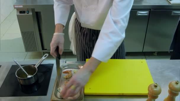 Professionelle Köche geben gehackte Pilze zusammen mit Garnelen und rühren Sauce