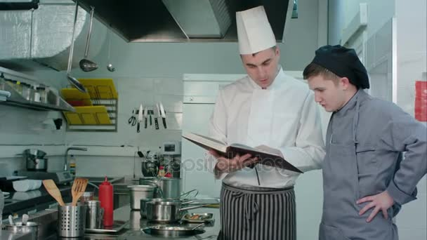 Šéf kuchař recept knihu a něco vysvětlovat jeho mladý praktikant