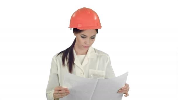 Mladý inženýr ženy nosit přilby zkoumání technické výkresy na bílém pozadí