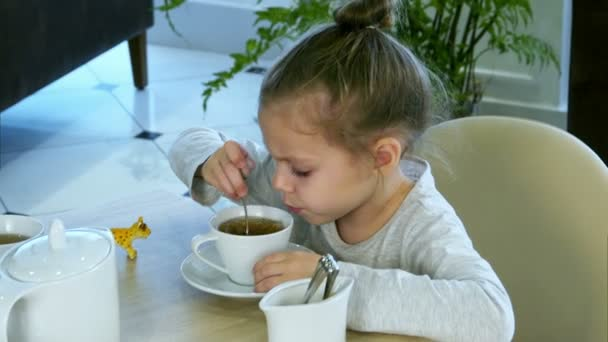Little russian girl holding spoon and stiring sugar in tea at restaurant.